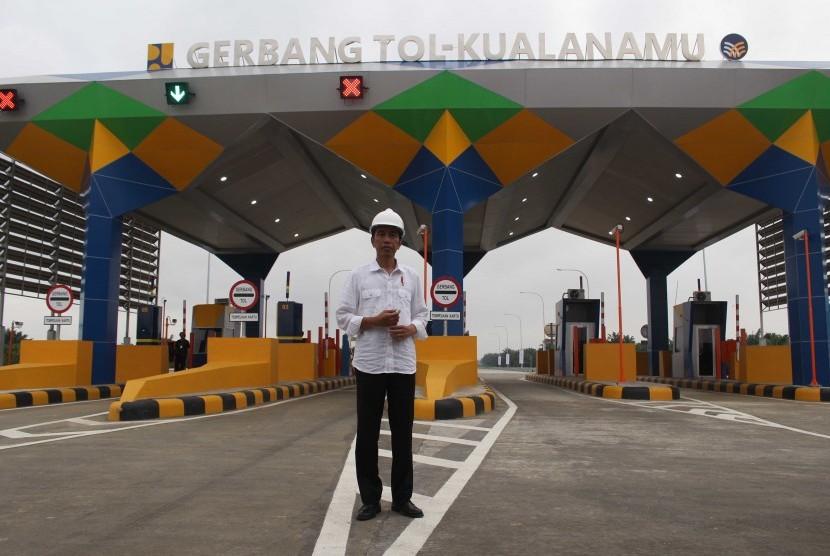 Presiden Joko Widodo berdiri di depan pintu masuk tol ketika meninjau Jalan Tol Trans Sumatera ruas gerbang tol Kualanamu saat diresmikan di Deli Serdang, Sumatera Utara, Jumat (13/10).