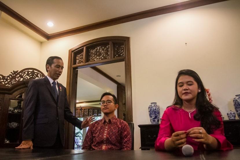 Presiden Joko Widodo bersama anaknya Kahiyang Ayu (kanan) dan Gibran Rakabumi Raka (tengah) memberikan keterangan terkait pernikahan anak keduanya di kediaman pribadi, Sumber, Solo, Jawa Tengah, Minggu (17/9).