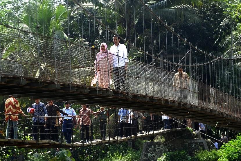 Presiden Joko Widodo bersama Ny Iriana Jokowi melewati jembatan gantung saat kunjungannya ke Lebak membagikan sembako dan uang kepada warga kurang mampu beberapa waktu lalu. (ilustrasi)