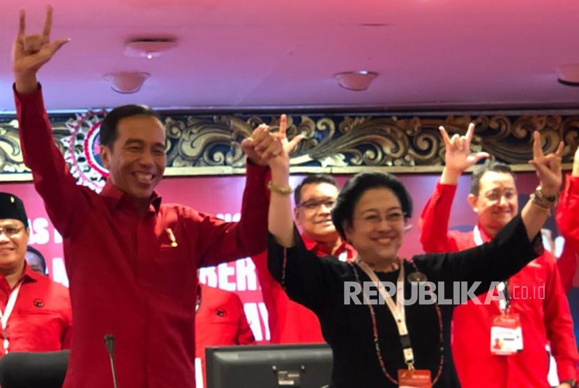 Presiden Joko Widodo dan Ketua Umum PDI Perjuangan Megawati Soekarnoputri berfoto sembari mengangkat tiga jari usai menetapkan kembali Joko Widodo sebagai Capres 2019.