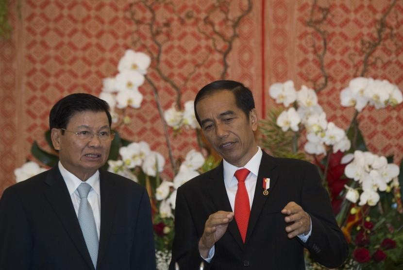 Presiden Joko Widodo (kanan) berbincang dengan Perdana Menteri Republik Demokratik Rakyat Laos Thongloun Sisoulith sebelum menyaksikan penandatangan nota kesepahaman bersama dalam kunjungan kenegaraan Laos di Istana Kepresidenan Bogor, Bogor, Jawa Barat, Kamis (12/10).