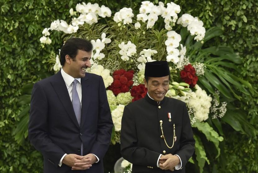 Presiden Joko Widodo (kanan) bersama Emir Qatar Sheikh Tamim bin Hamad Al Thani (kiri) tertawa disela-sela menyaksikan penandatanganan kerja sama kedua negara di Istana Bogor, Jawa Barat, Rabu (18/10).