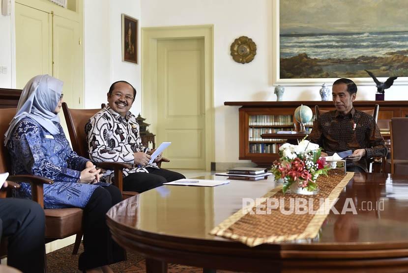 Presiden Joko Widodo (kanan) menerima Ketua Ombudsman Amzulian Rifai (kedua kiri) dan Wakil Ketua Ombudsman Lely Pelitasari Soebekty (kiri) di Ruang Kerja Presiden, Istana Kepresidenan Bogor, Jawa Barat, Kamis (7/12).
