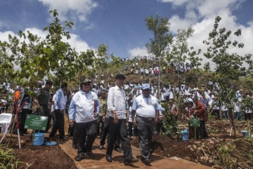Presiden Joko Widodo (kedua kanan) bersama Mentri Lingkungan Hidup, Siti Nurbaya Bakar (ketiga kanan) berjalan meninjau lahan kritis seusai menanam pohon jati saat acara Peringatan Hari Menanam Pohon Indonesia dan Bulan Menanam Nasional Tahun 2017 di Ponjong, Gunungkidul, DI Yogyakarta, Sabtu (9/12). Dalam acara yang digagas oleh Kementrian Linkungan Hidup itu sebanyak 45.000 pohon ditanam pada areal lahan kritis dan Presiden Joko Widodo meminta seluruh pihak terkait dan warga berkomitmen untuk merawat tanaman yang ditanam.