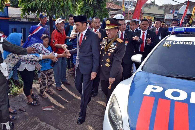 Presiden Joko Widodo (kedua kanan) didampingi Kapolri Jenderal Pol Tito Karnavian (kanan) menyapa warga ketika berjalan kaki menuju lokasi Upacara Parade dan Defile HUT ke-72 TNI Tahun 2017 di Dermaga Indah Kiat, Cilegon, Banten Kamis (5/10).