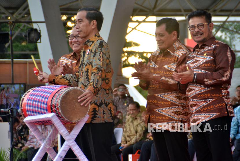 Presiden Joko Widodo (kedua kiri) di dampingi Menteri Koperasi dan UMKM, AA Gede Ngurah Puspayoga (kiri), Ketua Dewan Koperasi Indonesia, Nurdin Halid (kedua kanan), dan Gubernur Sulsel Syahrul Yasin Limpo (kanan) memukul gendang saat peringatan Hari Koperasi Nasional (Harkopnas) ke-70 di Lapangan Karebosi, Makassar, Sulawesi Selatan, Rabu (12/7).