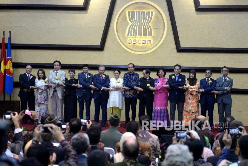 Presiden Joko Widodo (ketujuh kanan) bergandengan tangan dengan Sekjen ASEAN Le Luong Minh (keenam kanan), Menteri Luar Negeri Retno Marsudi (ketujuh kiri), dan perwakilan dari masing-masing negara anggota ASEAN berfoto bersama saat peringatan 50 tahun ASEAN di Sekretariat ASEAN, Jakarta, Jumat (11/8).