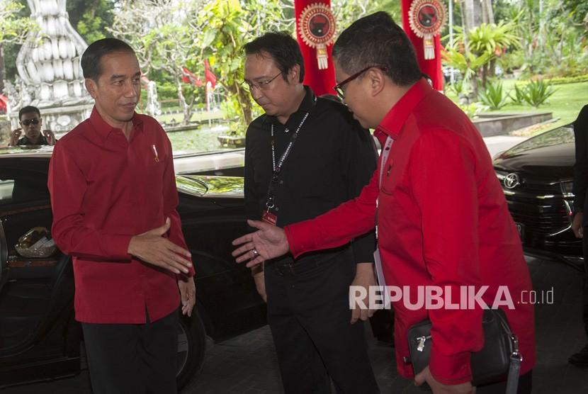 Presiden Joko Widodo (kiri) disambut oleh Sekjen DPP PDIP Hasto Kristiyanto (kanan) dan Panitia Pengarah Rakernas PDIP Prananda Prabowo dalam pembukaan Rakernas III PDIP di Sanur, Bali, Jumat (23/2).