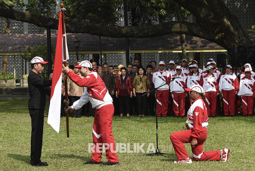 Presiden Joko Widodo (kiri) menyerahkan bendera Merah Putih kepada Ketua Kontingen Indonesia SEA Games XXIX Malaysia Aziz Syamsuddin (kedua kiri) saat upacara pelepasan di halaman Kompleks Istana Kepresidenan, Jakarta, Senin (7/8).