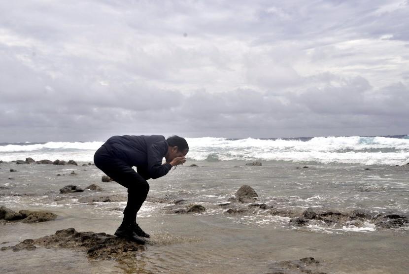Presiden Joko Widodo membasuh wajah dengan air laut di pantai Pulau Miangas, Kabupaten Kepulauan Talaud, Sulawesi Utara, Rabu (19/10).