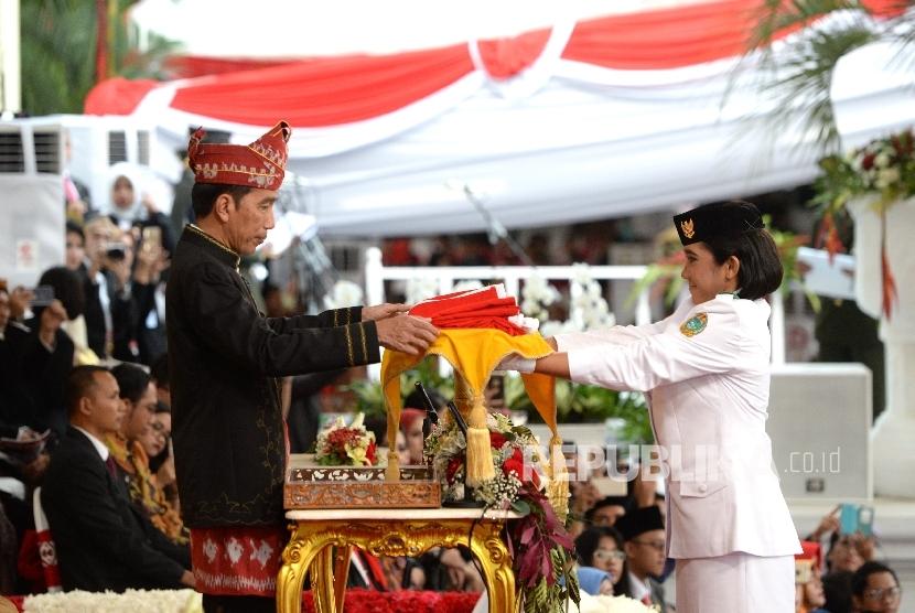 Presiden Joko Widodo menerima bendera pusaka merah putih dari anggota Paskibraka Ruth Cheliine Eglesya Purba pada Upacara Hari Kemerdekaan ke-72 di Istana Merdeka, Jakarta, Kamis (17/8). P