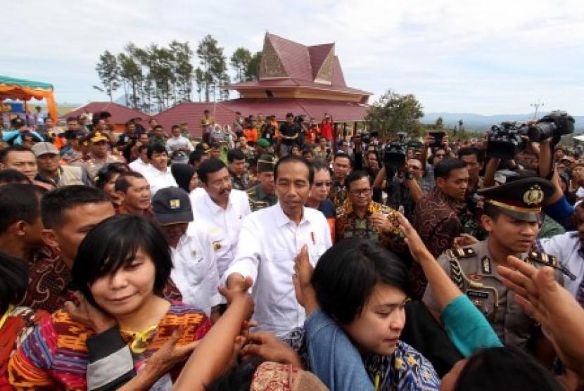 Presiden Joko Widodo menyapa warga saat tiba di kawasan perumahan relokasi pengungsi Gunung Sinabung di Desa Siosar, Karo, Sumatra Utara, Sabtu (14/10). Perumahan untuk relokasi pengungsi Sinabung yang dipersiapkan sebanyak 370 rumah baru itu akhirnya selesai dan telah dihuni oleh para pengungsi.