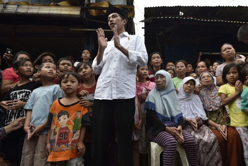 President Joko Widodo (central) was talking to residents after giving basic necessities parcel at Duri Kepa, Jakarta, Thursday (June 22).