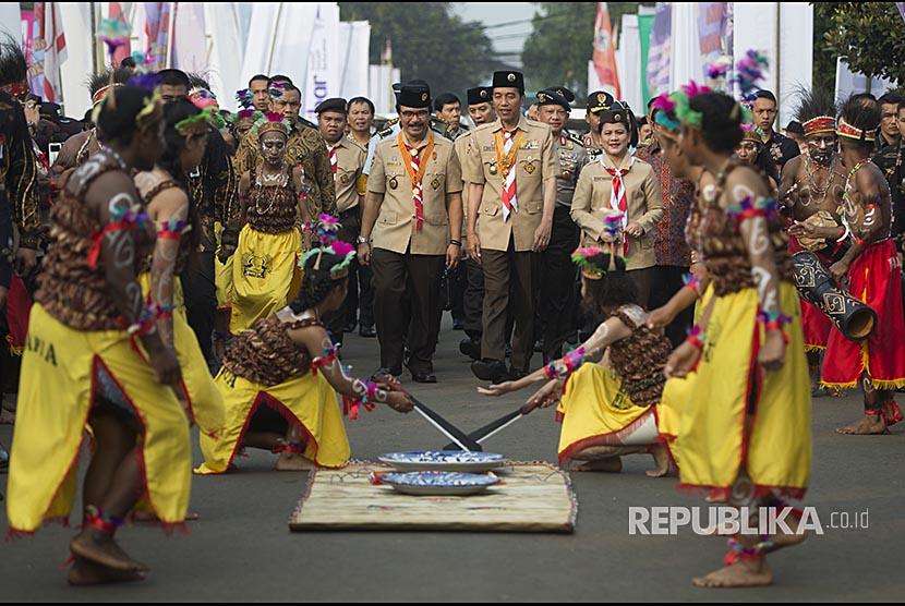 Presiden Joko Widodo (tengah) berjalan bersama Ibu Negara Iriana Joko Widodo (kanan) dan  Ketua Kwartir Nasional Gerakan Pramuka Adhyaksa Dault (kiri) mengikuti prosesi Raimuna Nasional XI
