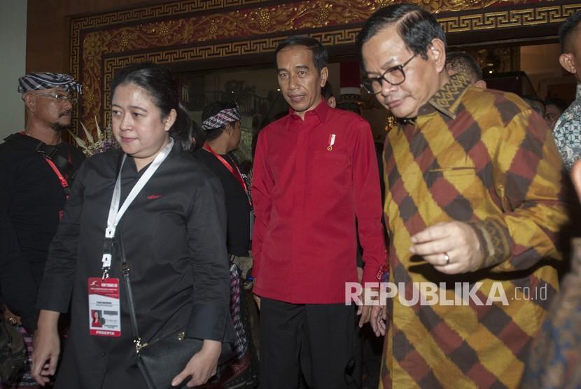 Presiden Joko Widodo (tengah) berjalan bersama Sekretaris Kabinet Pramono Anung (kanan) dan Menko Bidang Pembangunan Manusia dan Kebudayaan yang juga kader PDIP Puan Maharani (kiri) seusai pembukaan Rakernas III PDIP di Sanur, Bali, Jumat (23/2).