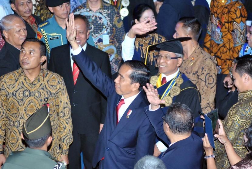 Presiden Joko Widodo (tengah) bersama Rektor IPB Herry Suhardiyanto (kedua kanan) melambaikan tangan kepada mahasiswa saat sidang terbuka di Grha Widya Wisuda, Kampus IPB, Dramaga, Kabupaten Bogor, Jawa Barat, Rabu (6/9).