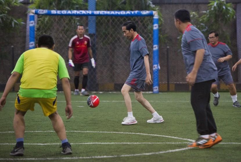Presiden Joko Widodo (tengah) berusaha mengontrol bola saat bermain futsal di Lapangan Futsal Time, Kelapa Gading, Jakarta, Selasa (7/2).