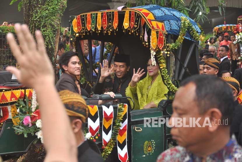 Presiden Joko Widodo (tengah) dan Ibu Negara Iriana Joko Widodo (kanan) bersama putra bungsu Kaesang Pangarep (kiri) berada di dalam kereta kencana saat Kirab Kereta Kencana Pengantin melintas di Jalan Gagak Hitam, di Medan, Sumatra Utara, Ahad (26/11).