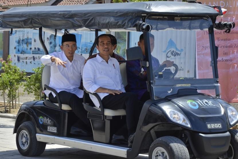 Presiden Joko Widodo (tengah) didampingi Gubernur NTB TGB Zainul Majdi (kiri) berkeliling kawasan di sela-sela peresmian operasional KEK Mandalika, di Desa Kuta, Pujut, Praya, Lombok Tengah, NTB, Jumat (20/10).