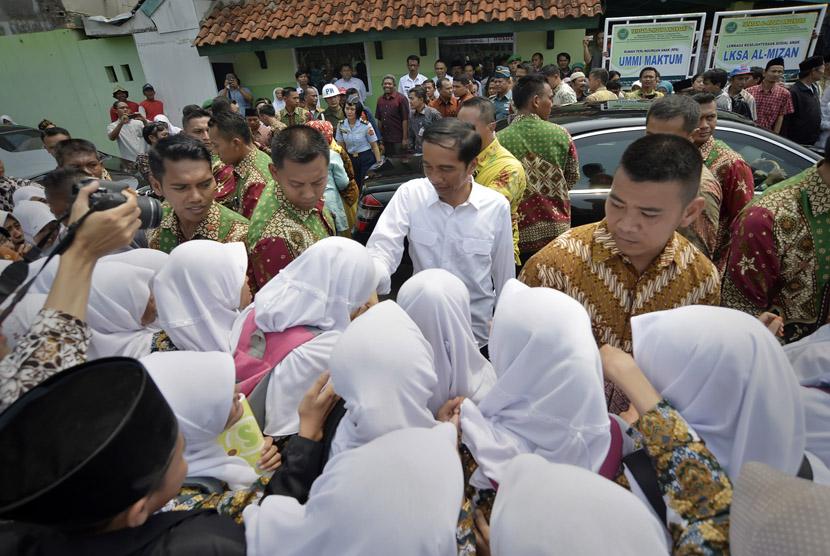 Presiden Joko Widodo (tengah) menyapa santri saat mengunjungi Pondok Pesantren Al Mizan Jatiwangi, Majalengka, Jawa Barat beberapa waktu lalu..