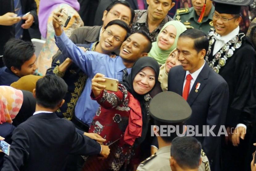 Presiden RI Joko Widodo berfoto bersama para undangan saat hadir pada puncak perayaan Dies Natalis ke-60 Unversitas Padjadjaran (Unpad), di Graha Sanusi Hardjadinata, Kampus Unpad, Kota Bandung, Senin (11/9).