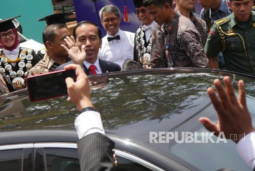 Presiden RI Joko Widodo (Jokowi) melambaikan tangan usai hadir menyampaikan orasi ilmiah pada puncak perayaan Dies Natalis ke-60 Unversitas Padjadjaran (Unpad), di Graha Sanusi Hardjadinata, Kampus Unpad, Kota Bandung, Senin (11/9).
