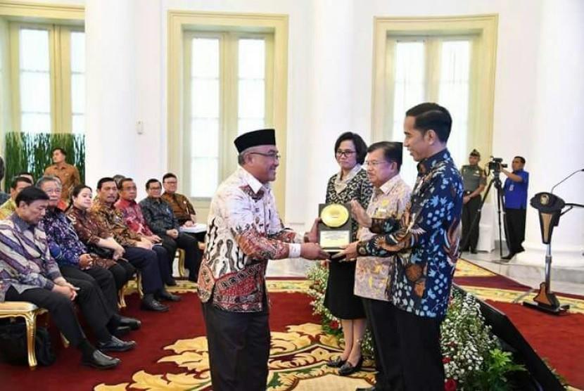 Presiden RI Joko Widodo menyerahkan penghargaan Anugerah Dana Rakca 2017 dari Kementerian Keuangan RI kepada Wali Kota Depok Mohammad Idris di Istana Bogor, Rabu (6/12).