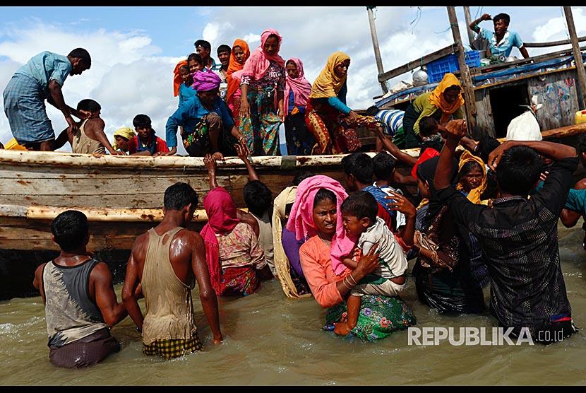 Puluhan pengungusi Rohingya turun dari perahu setibanya di pesisir Teluk Bengal, di Shah Porir Dwip, Bangladesh, Selasa (11/9)