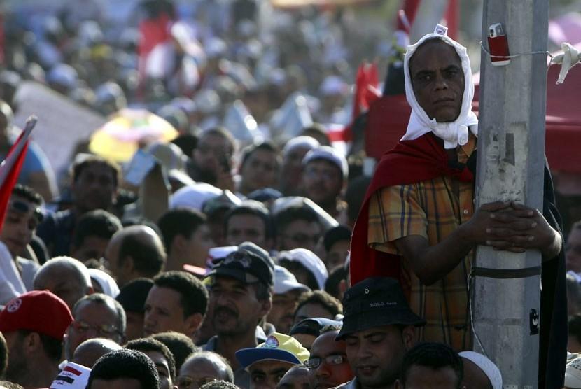 Presiden Mesir terpilih Muhammad Mursi melambaikan tangan pada puluhan ribu pendukungnya yang berkumpul di Tahrir Square, Kairo.   (Amr Nabil/AP)