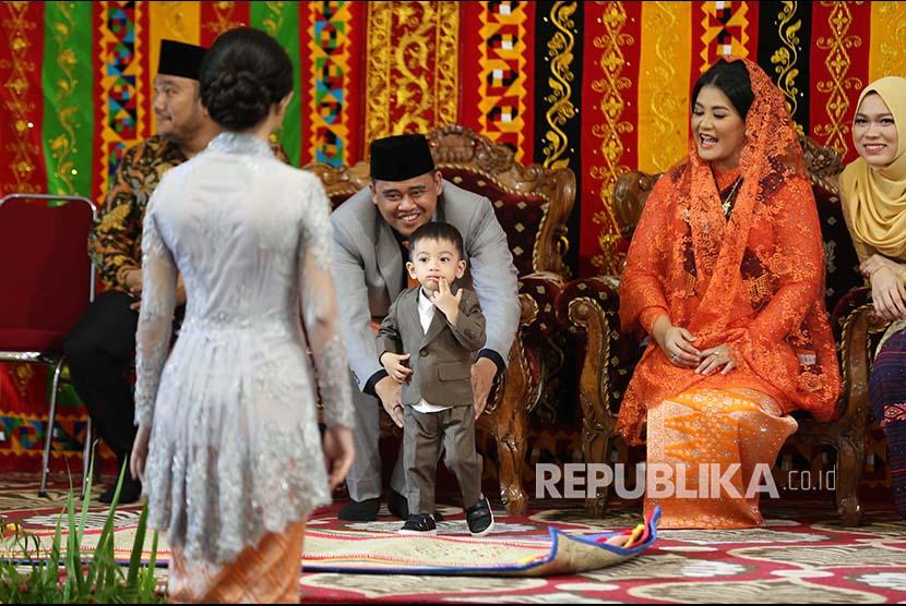 Putri Presiden Joko Widodo, Kahiyang Ayu (kedua kanan) bersama suaminya Bobby Afif Nasution memegang Ethes anak Gibran Rakabuming di sela ritual adat
