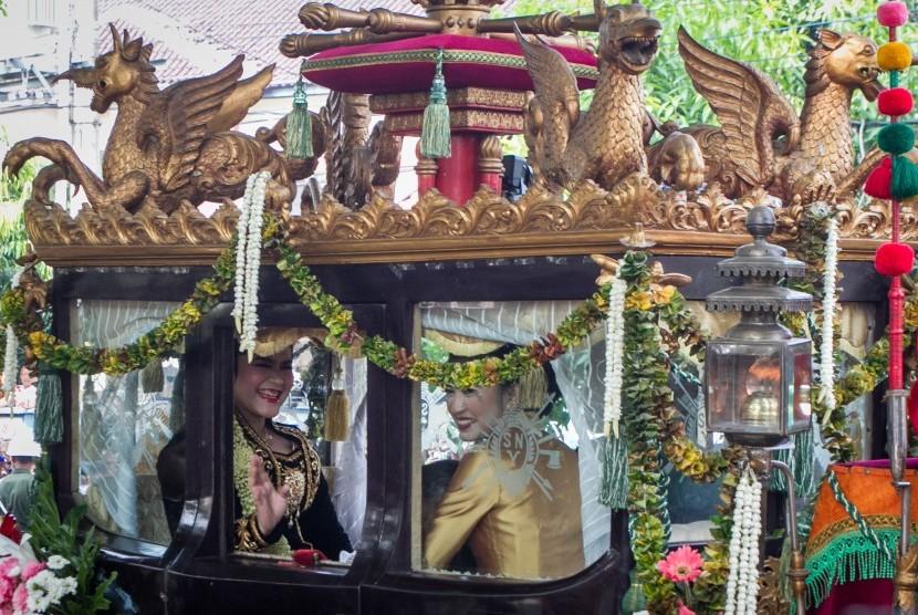 Putri Presiden Joko Widodo, Kahiyang Ayu, melambaikan tangan saat naik kereta kencana menuju acara ijab dan resepsi pernikahan di Graha Saba Buana, Solo, Jawa Tengah, Rabu (8/11).