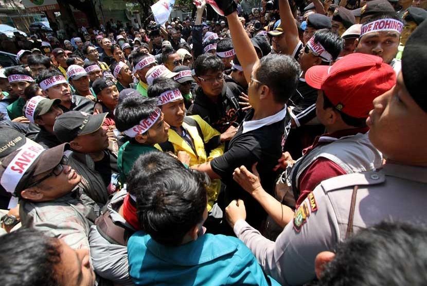 Ratusan demonstran yang tergabung dalam Masyarakat Peduli Rohingya melakukan aksi dorong ketika berunjuk rasa di depan Kedutaan Besar Myanmar, Jakarta, Kamis (9/8). (M Agung Rajasa/Antara)
