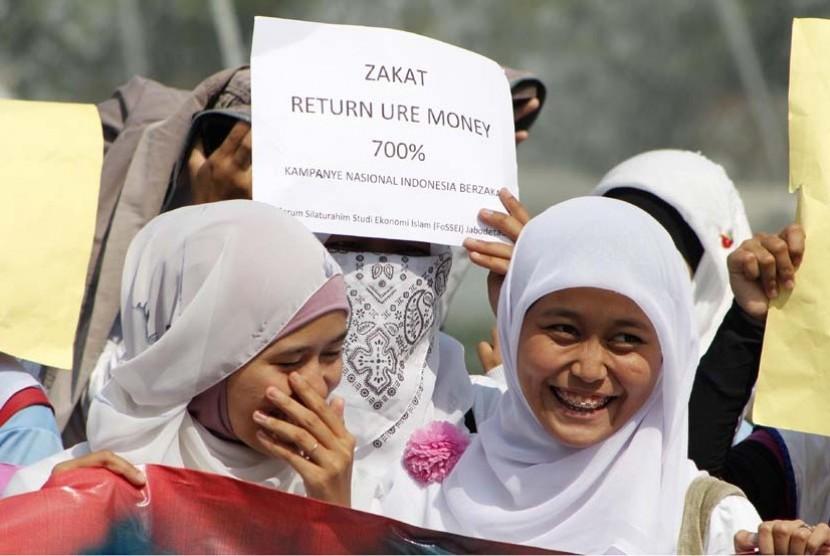 Ratusan mahasiswa Forum Silaturahim Studi Ekonomi Islam (FoSSEI) melakukan kampanye Indonesia Berzakat di Kawasan Bundaran Hotel Indonesia, Jakarta, Ahad (13/5). (Adhi Wicaksono/Republika)