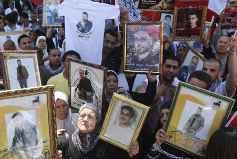 Ratusan warga Palestina memegang foto anggota keluarga mereka yang ditahan di penjara Israel dalam unjuk rasa di Kota Nablus, Tepi Barat, Palestina, Selasa (17/4).