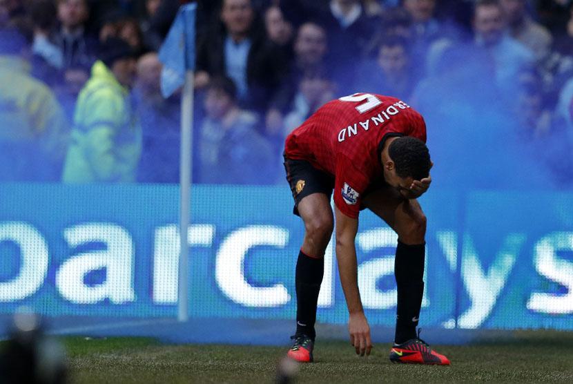 Reaksi pemain Manchester United Rio Ferdinand, setelah dihantam oleh sebuah benda yang dilemparkan dari arah penonton saat bertanding melawan Manchester City di Stadion Etihad di Manchester,Ahad (9/12). (Reuters/Phil Noble)