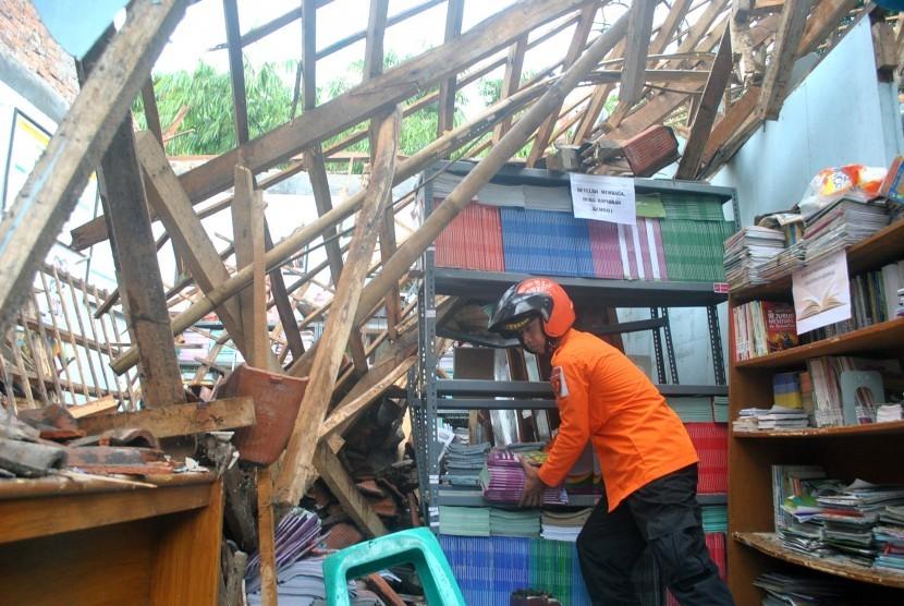 Relawan Badan Penanggulangan Bencana Daerah (BPBD) Kota Bogor mengangkat buku pelajaran dari ruang perpustakaan yang ambruk di SDN Pakuan, jalan Dahlia, Kelurahan Pakuan, Kota Bogor, Jawa Barat, Minggu (12/2).