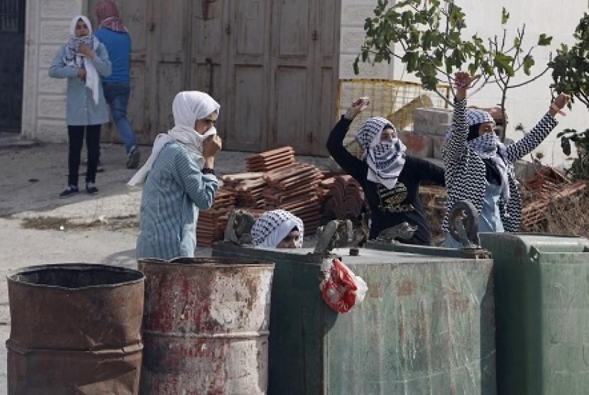 Remaja putri Palestina melemparkan batu ke aparat Israel