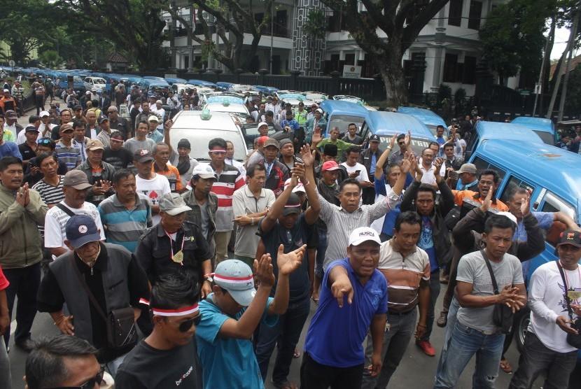 Ribuan supir angkutan melakukan mogok massal dan berunjuk rasa menolak keberadaan transportasi berbasis aplikasi online di depan Balaikota Malang, Jawa Timur, Selasa (26/9).