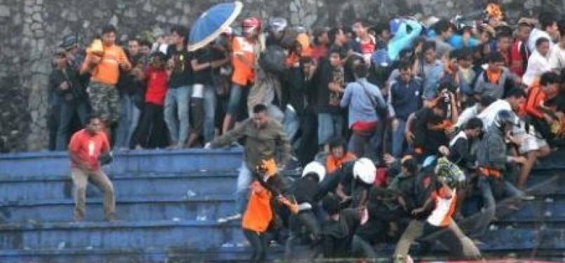 Ribuan suporter saling lempar dan saling pukul pada pertandingan Indonesia Super League (ISL) antara Persija Jakarta dan Persipura Jayapura di Stadion Mandala Krida, Yogyakarta, Selasa (7/2).