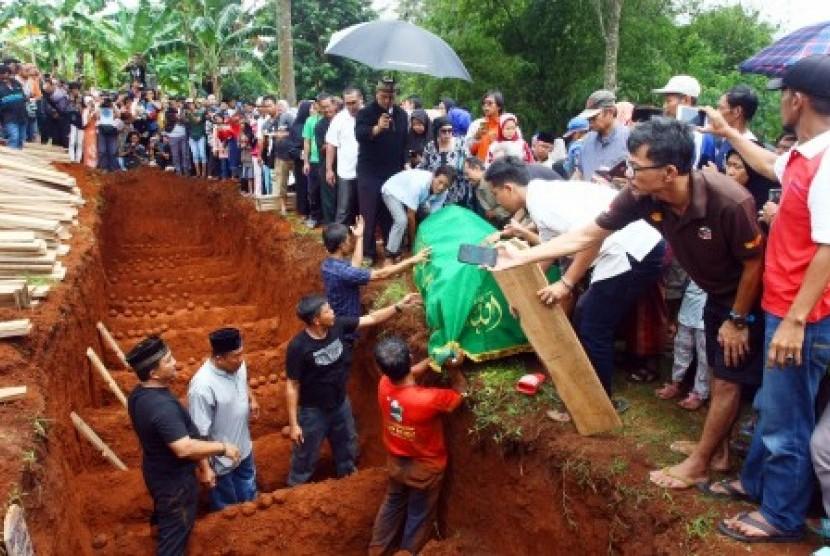 Ribuan warga menyaksikan prosesi pemakaman korban kecelakaan bus di tanjakan Emen, Subang, di Tempat Pemakaman Umum (TPU) Legoso Ciputat, Tangerang Selatan, Banten, Ahad (11/2). Sebanyak 26 orang korban tewas kecelakaan bus pariwisata di tanjakan Emen, Subang yang kesemuanya warga Legoso Ciputat, dimakamkan secara massal.