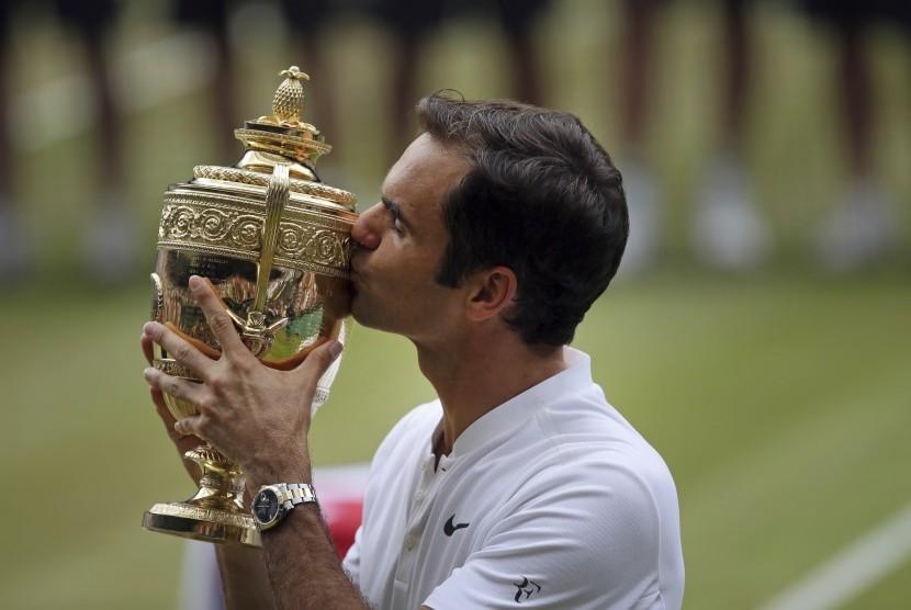 Roger Federer mencium trofi Wimbledon setelah mengalahkan Marin Cilic pada partai final, Ahad (16/7).
