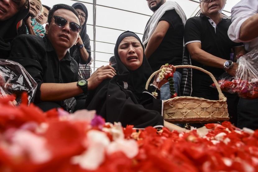 Almyanda Safira (tengah) ibunda dari korban tewas dalam kasus pembunuhan Pulomas Dianita Gemma Dzalfayla dan Diona Arika Andra Putri menaburkan bunga di makam kedua anaknya di TPU Tanah Kusir, Jakarta, Rabu (28/12).