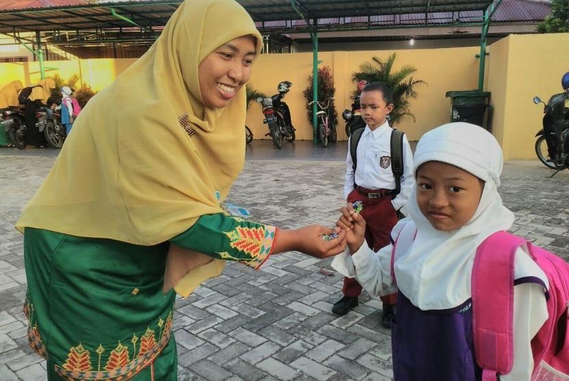 Salah satu guru di PAUD Juara Pekanbaru sedang memberikan permen kepada siswa saat hari pertama sekolah.