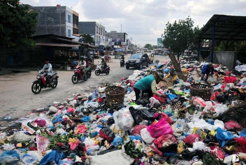 Sampah menumpuk memenuhi badan jalan di Jalan Rajawali, Kota Pekanbaru, Selasa (7/6). Tumpukan sampah kini banyak ditemukan di sudut Kota Pekanbaru setelah upaya pemerintah daerah untuk menswastanisasi layanan angkut sampah melalui PT Multi Inti Guna (MIG)