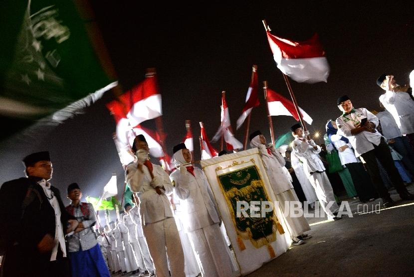 Santri membawa Pataka NU dan Bendera Merah Putih saat kirab peringatan Hari Santri Nasional di Masjid Raya KH Hasyim Asyari, Jakarta, Sabtu (21/10) malam.