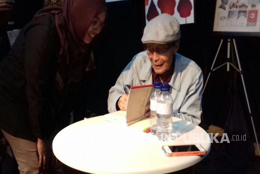 Sapardi Djoko Damono menandatangani buku-buku yang dibeli penggemar puisinya dalam acara 77 Tahun Sapardi Djoko Damono, Launching 7 Buku dan Nyanyian Puisi.