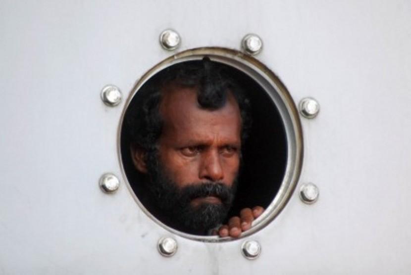 Satu dari sejumlah imigran gelap asal Srilanka yang dievakuasi Tim Basarnas melihat dari jendela kapal saat akan dipindahkan ke daratan, di Pelabuhan Teluk Bayur, Padang, Sumbar, Rabu (2/1/2013)