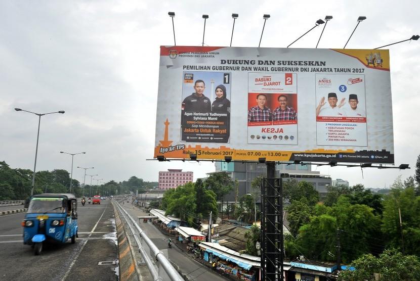 Sebuah angkutan umum melintas di dekat baliho sosialisasi Pilkada Gubernur dan Wakil Gubernur DKI Jakarta Tahun 2017 di Jakarta, Jumat (10/2).