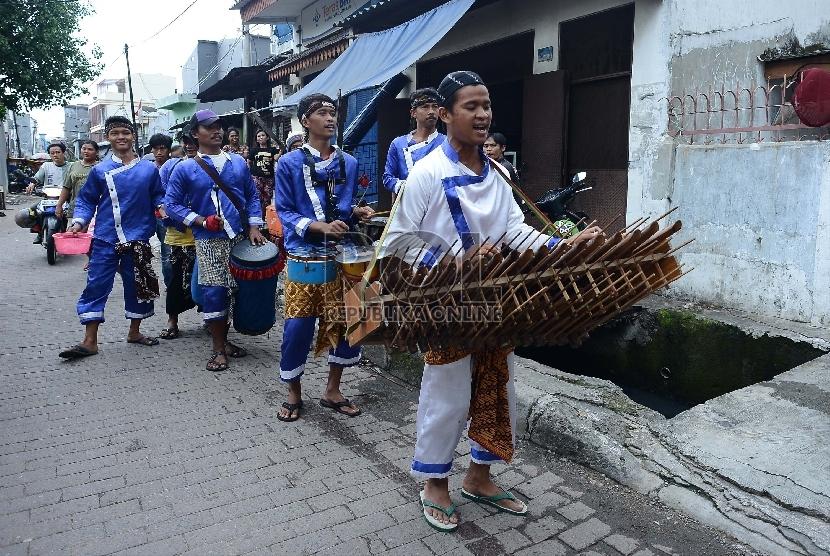 Sebuah grup musik dengan menggunakan alat musik tradisional mengamen di kawasan Glodok, Jakarta Pusat, Rabu (25/2).