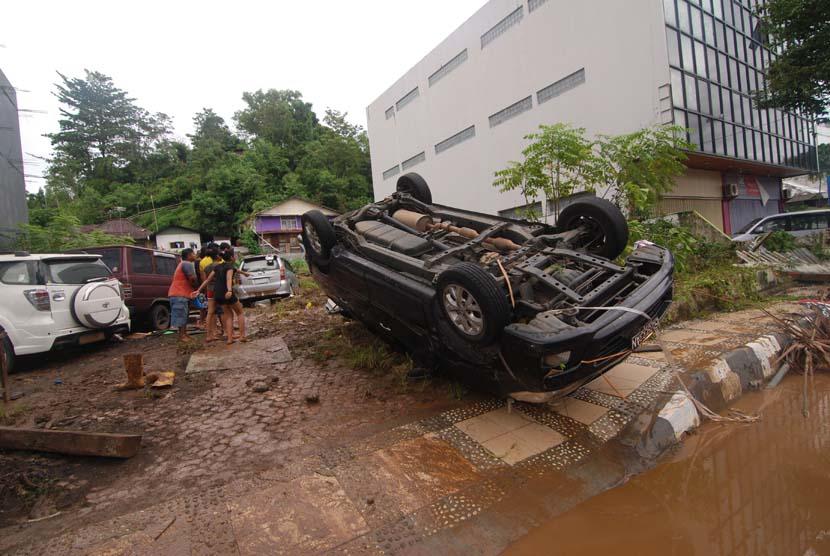 Sebuah mobil terbalik akibat terseret bajir di kawasan kantor Walikota Manado, Sulawesi Utara, Kamis (16/1).     (Antara/Fiqman Sunandar)